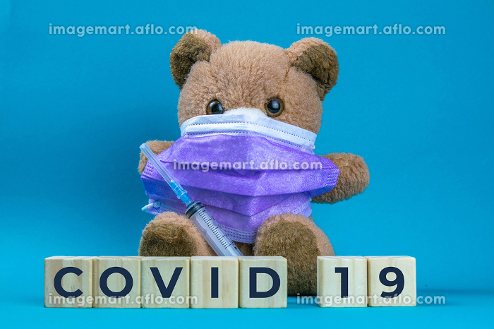 Covid 19. Coronavirus. Big teddy bear are sitting in blue medical masks on a blue background, concept of protection from respiratory disease, virus, and individual respiratory protectionの販売画像
