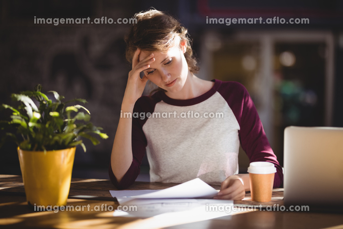Troubled young female designer reading paper at coffee shopの販売画像
