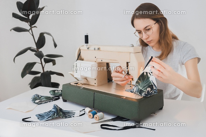 Girl sewing protective medicine mask on sewing machine at home to prevent the flu. Covid-19 in the room with white background, Rivne, Rivne Oblast, Ukraineの販売画像