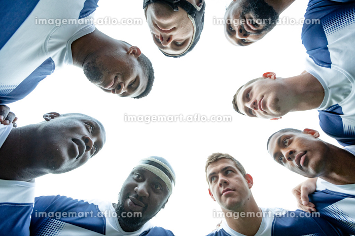 Bottom view of group of male rugby players forming huddles in stadiumの販売画像