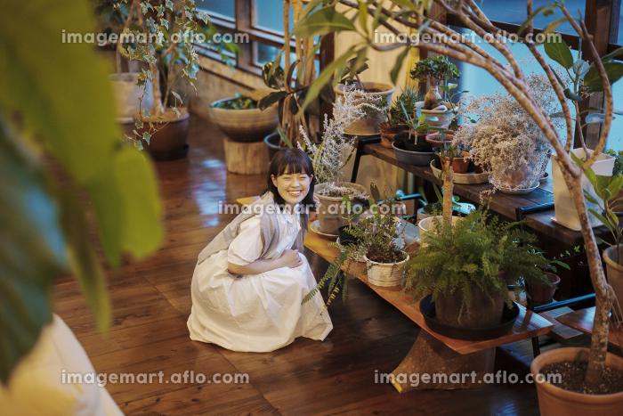笑顔で観葉植物の様子を見る若い女性の販売画像