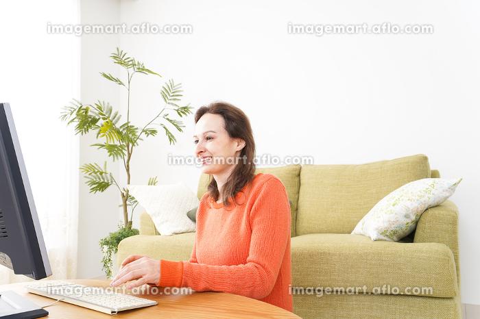 自宅でパソコンを使う若い女性の販売画像