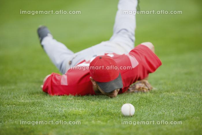芝の上の野球ボールとユニフォームを着た選手の販売画像