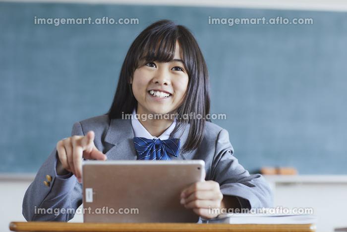 タブレットで授業を受ける女子中学生の販売画像