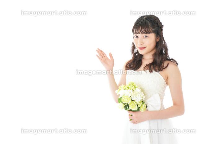 ブーケを持ち指差す花嫁の女性の販売画像