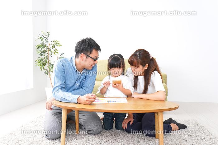 子どもに教育をする両親の販売画像