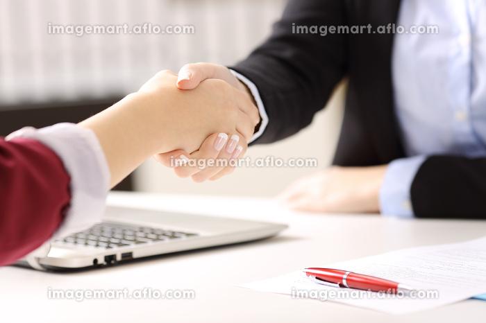 Businesswomen handshaking closing a dealの販売画像