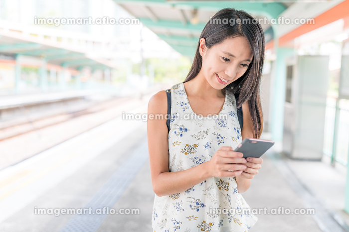 Woman using cellphone on light rail station in Hong Kong cityの販売画像