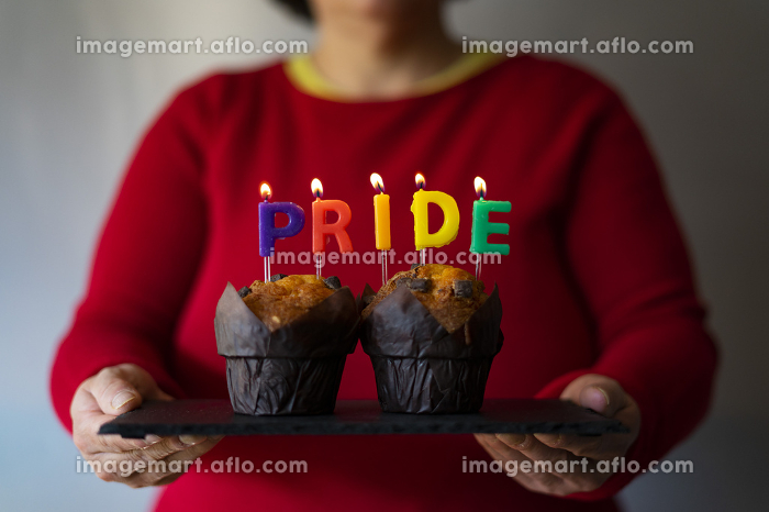 Woman picking up a plate with muffins and Pride candles.の販売画像