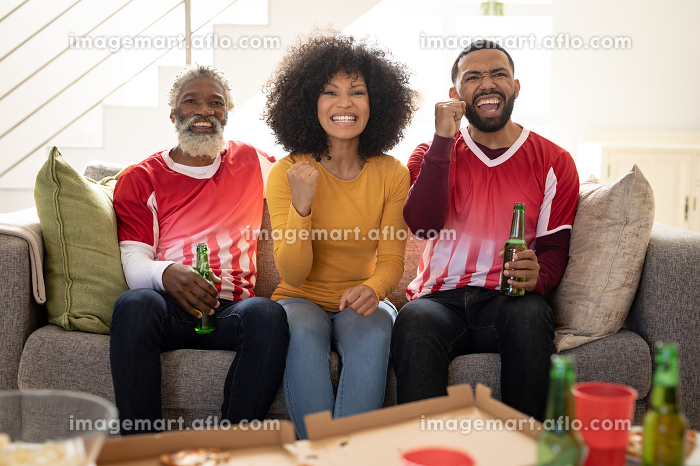 Multi generation African American man and cou at home sitting on sofa in living room, watching sports on TV cheering with arms in the air. Family spending quality time at home together in slow motion.の販売画像