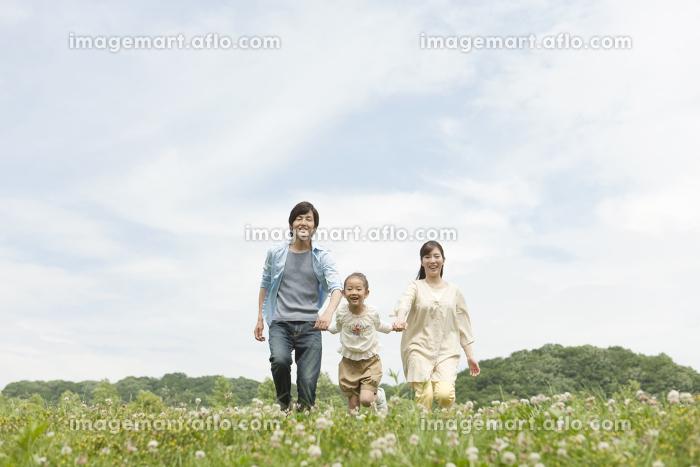 手をつないで走る家族3人の販売画像