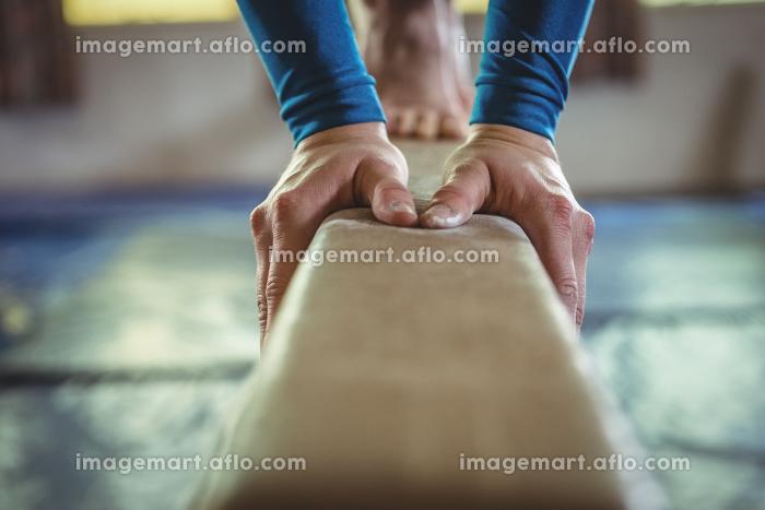 Female gymnast practicing gymnastics on the balance beamの販売画像