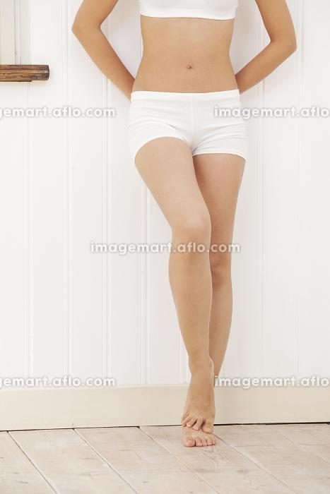 壁に寄りかかる女性の脚の販売画像