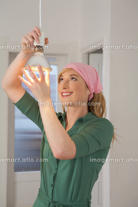 Young woman changing light bulb smiling