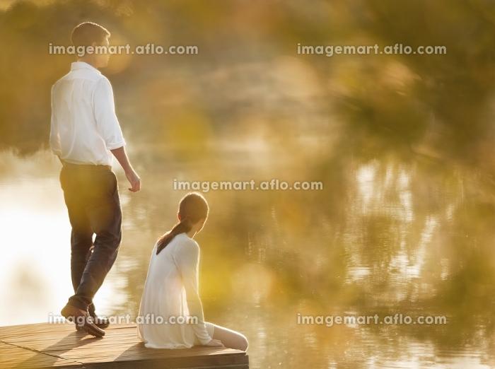 Couple relaxing on dock of lakeの販売画像