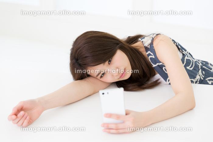 部屋でスマホを見る女性 考えるの販売画像