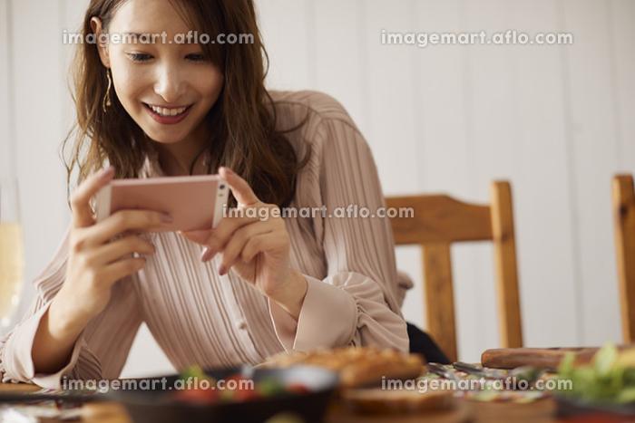 スマートフォンで料理の写真を撮る日本人女性