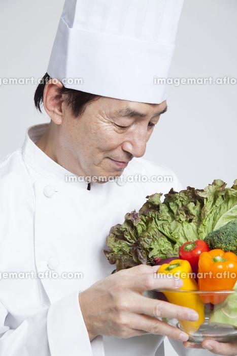 野菜を持って微笑む調理師の販売画像