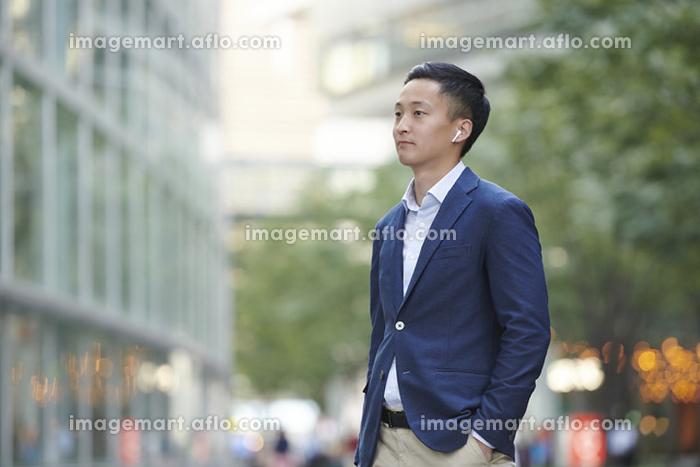ワイヤレスイヤホンで音楽を聴く若い日本人男性