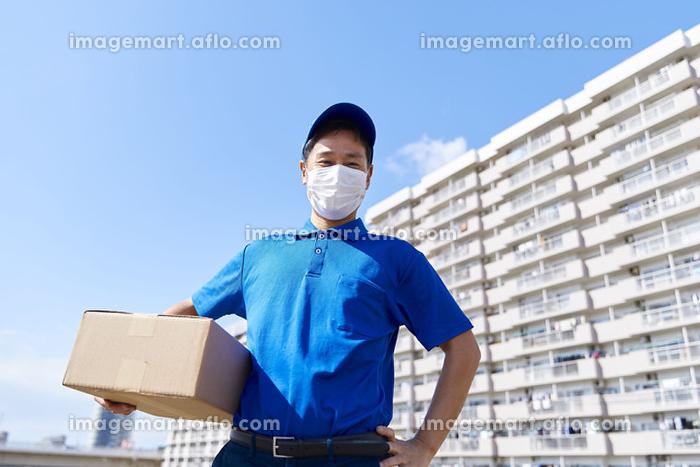 マスクを付けている配達員の販売画像
