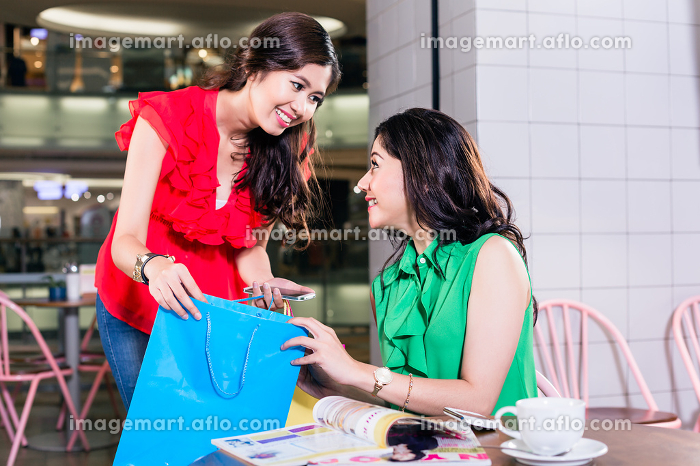 Cheerful woman showing to her best friend her purchaseの販売画像