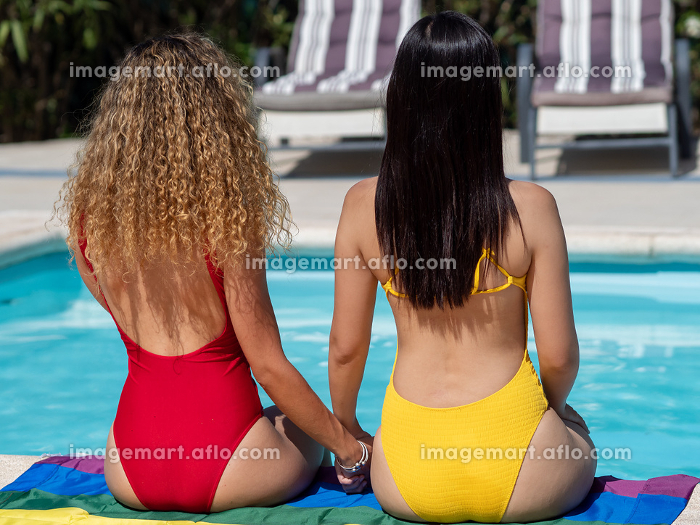 Two girls from different ethnic groups sit on an lgtb flag at the edge of the pool with their backs and hands heldの販売画像