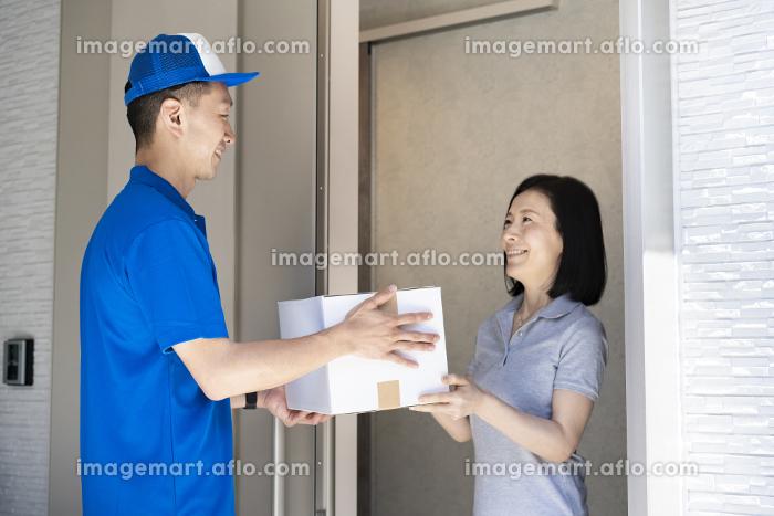 荷物を手渡す男性スタッフと、受け取る女性の販売画像