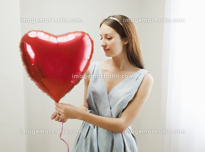 Woman holding heart shaped balloonの販売画像