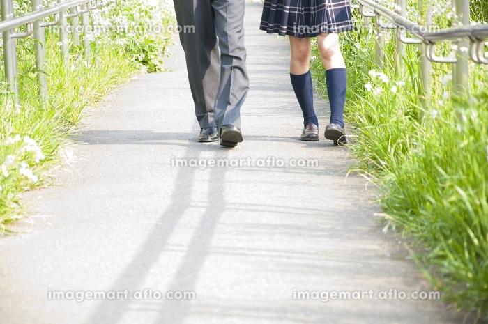 並んで歩く高校生カップルの足元の販売画像