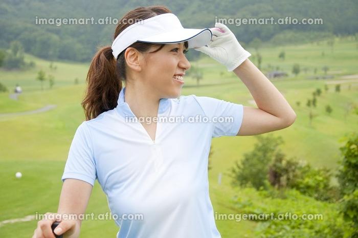 ゴルフクラブを持って遠くを見る女性の販売画像