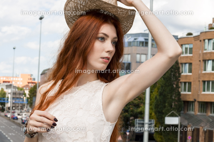 attractive young woman with long hair and straw hat outdoors rootenの販売画像