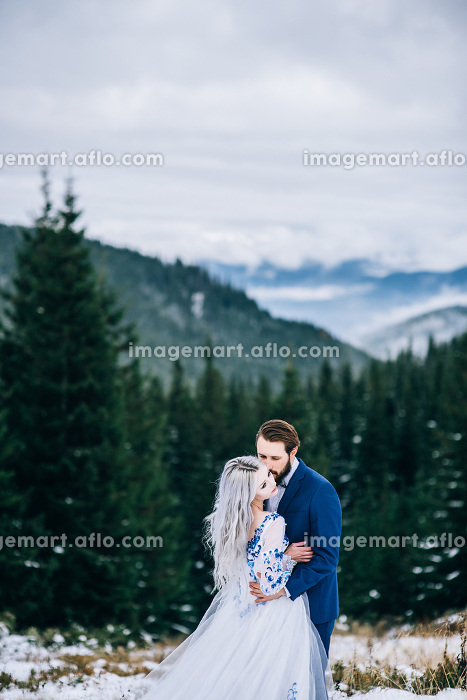 groom in a blue suit and bride in white in the mountains Carpathiansの販売画像
