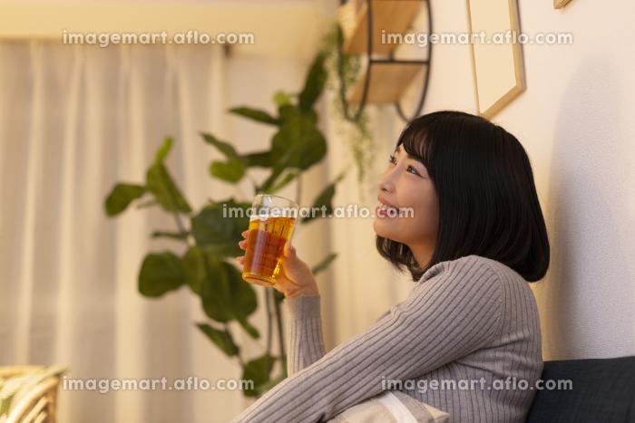 夜の部屋でビールを飲む若い女性の販売画像