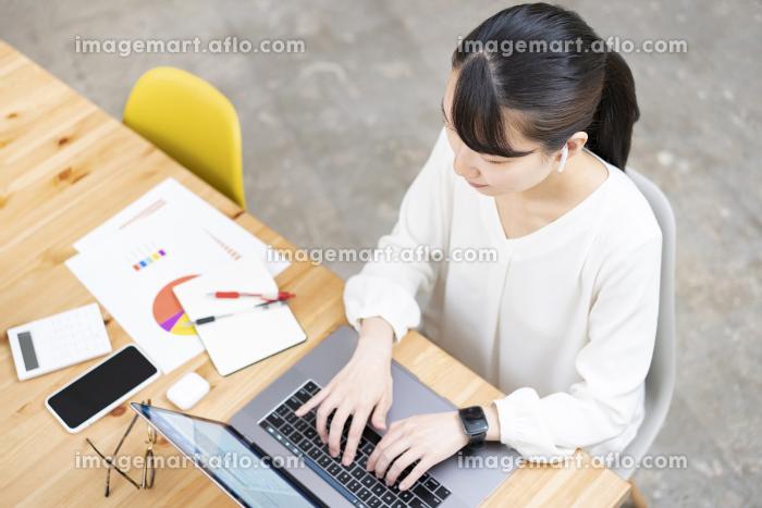 カジュアルな空間で仕事をする女性の販売画像