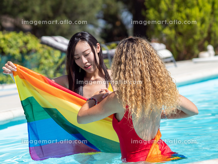 Stock photo of two girls of different ethnicities in the water of a swimming pool with a raised lgtb flagの販売画像