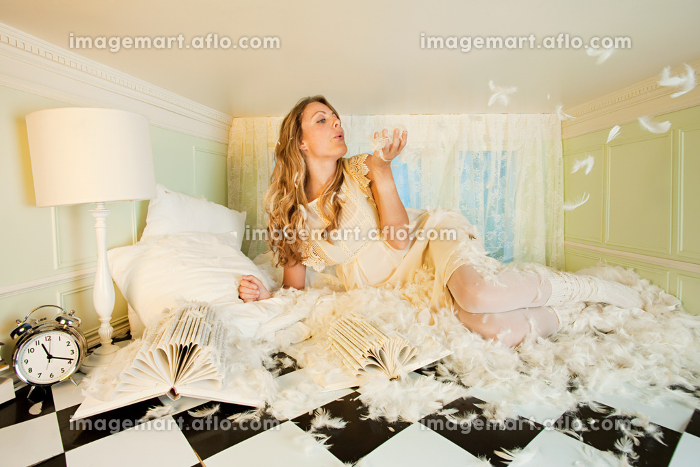 Young woman in small room, blowing pillow feathers