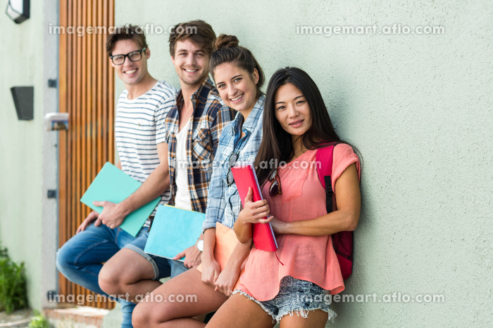 Hip friends leaning against wall and holding notebooks