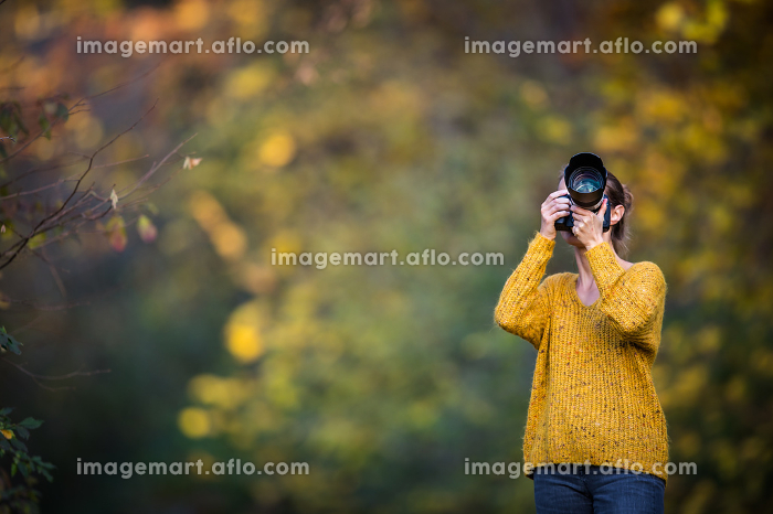 Pretty, female photographer taking pictures outdoor on a lovely autumn day - shallow DOF, color toned imageの販売画像