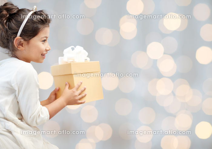 happy little girl with present over lights