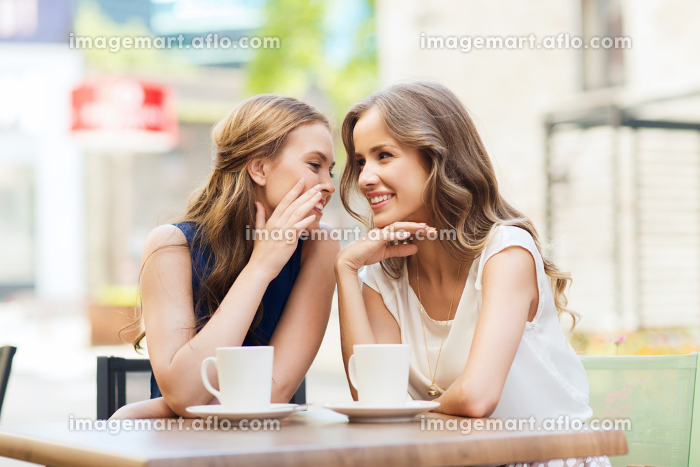 young women drinking coffee and talking at cafeの販売画像