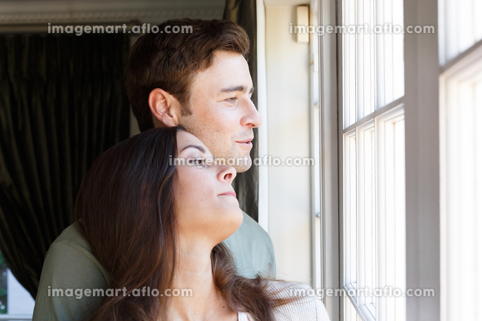Caucasian couple looking out of window smiling woman leaning on man. self isolation at home during covid 19 coronavirus pandemic.の販売画像