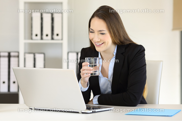Office worker working holding a glass of waterの販売画像