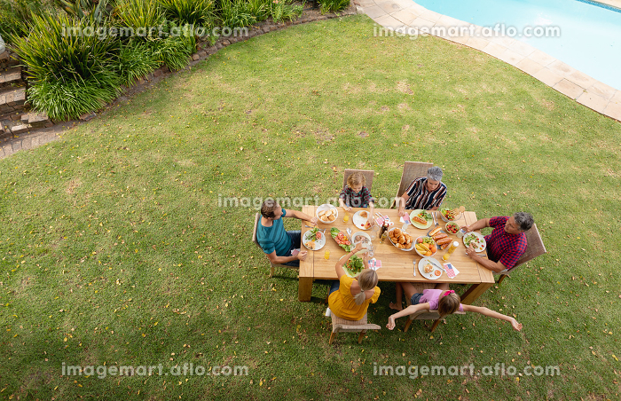 High angle view of caucasian three generation family sitting at table eating meal in garden. three generation family celebrating independence day eating outdoors together.の販売画像