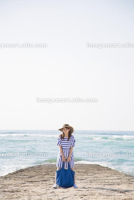 海岸でバッグを持って立つ日本人女性の販売画像