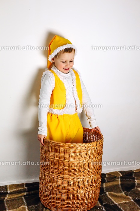 Cute smiling boy in yellow gnome elf outfit stand in wicker basketの販売画像