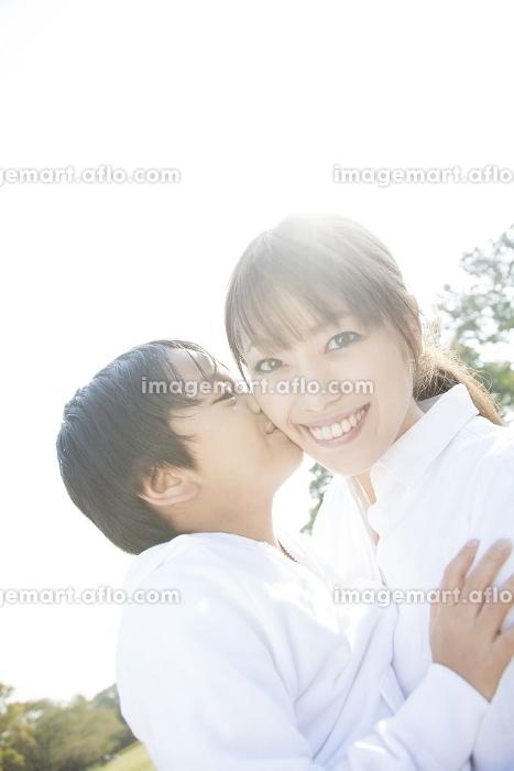 母の頬にキスする男児の販売画像