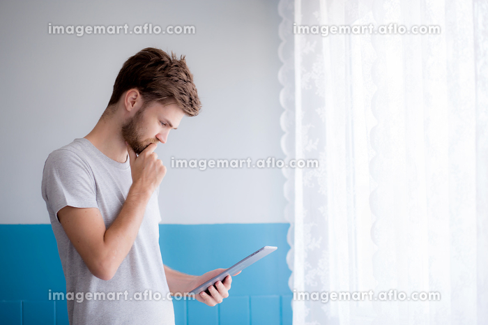 Closeup view of pensive bearded man using tablet while standingの販売画像