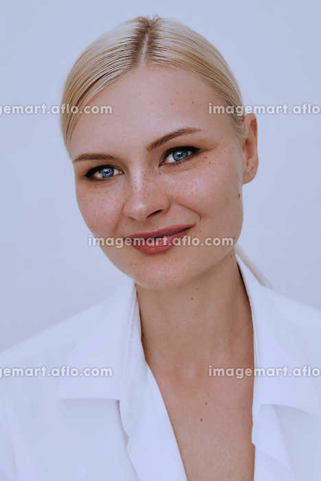 Beautiful young smiling clever blonde freckles woman on white wall. Pretty female wearing white shirt. Friendly natural casual portrait.の販売画像