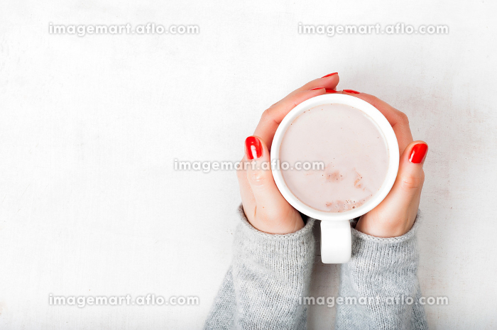 Woman with red fingernaild holding cup of hot cacao beverage on white wooden backgroundの販売画像