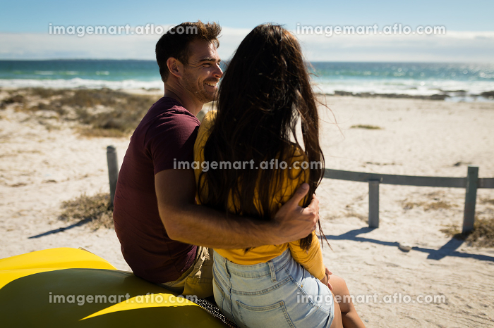Happy caucasian couple sitting on beach buggy by the sea embracing. beach break on summer holiday road trip.の販売画像